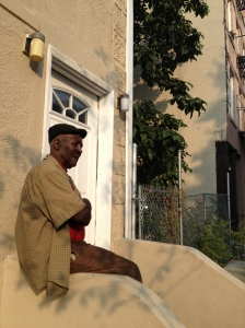 Raphael Ford sits on his stoop at 501 President Street in Brooklyn. He opposes an urban farm moving in on the empty lot next door.