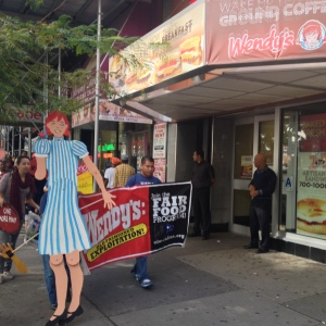 Representatives of Wendy's International stand outside of a Wendy's restaurant on East 14th Street in Manhattan as protesters picket, demanding the chain agree to help improve working conditions on Florida tomato farms. (Photo Credit: Leif Skodnick)