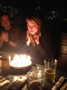 Jenna Dagenhart prepares to blow out her birthday candles while John Ismay applauds.